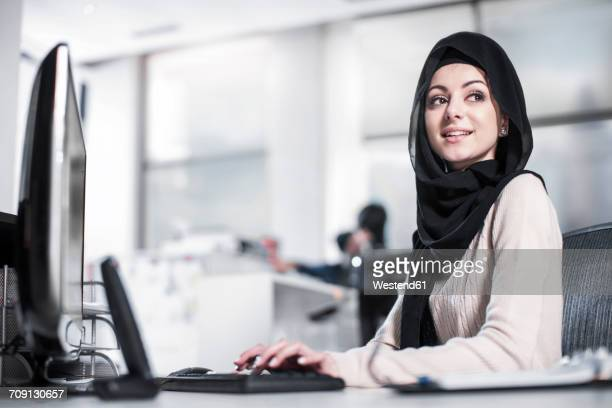 Young woman wearing hijab working on desk in office