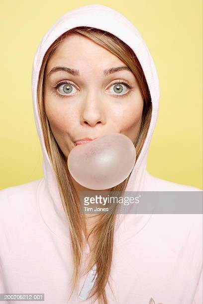 Young woman wearing hood, blowing bubble, portrait