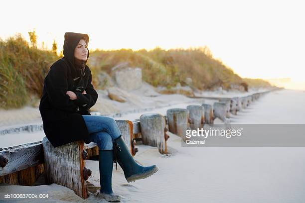 Young woman wearing hooded jacket, looking away