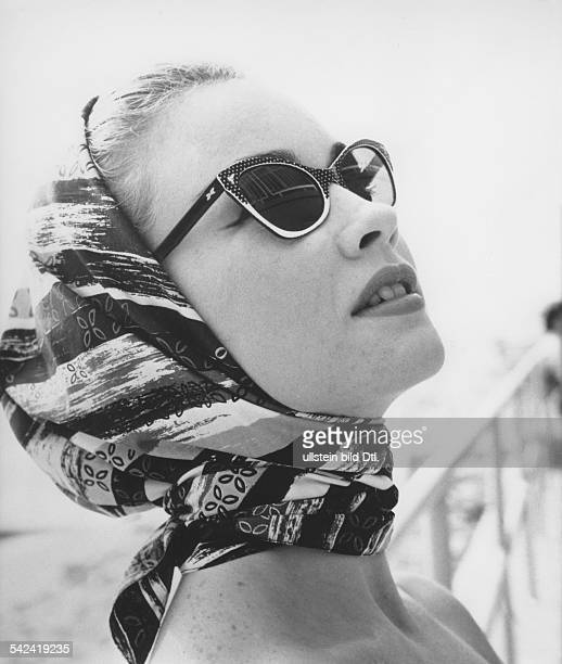 A young woman wearing hornrimmed sunglasses with white dots 1956