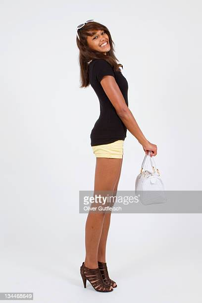 Young woman wearing hot pants and high heels, holding a white handbag, standing