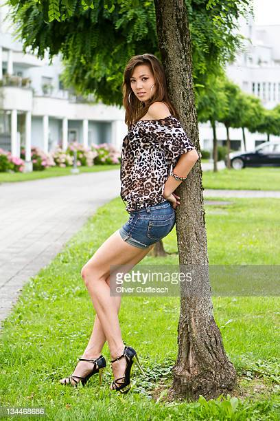 Young woman wearing hot pants, leopard-print top and high heels leaning against tree