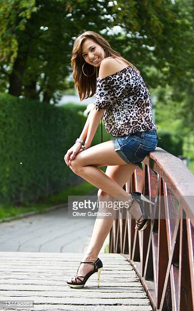 Young woman wearing hot pants, leopard-print top and high heels leaning against wooden balustrade of a wooden bridge