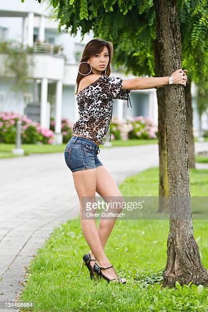 Young woman wearing hot pants, leopard-print top and high heels, posing with a tree