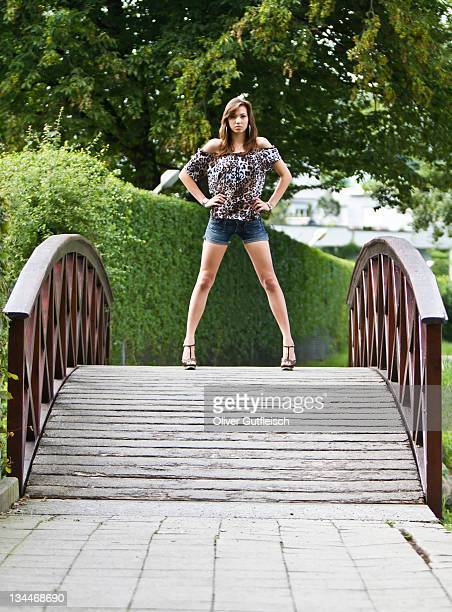 Young woman wearing hot pants, leopard-print top and high heels posing confidently on curved wooden bridge
