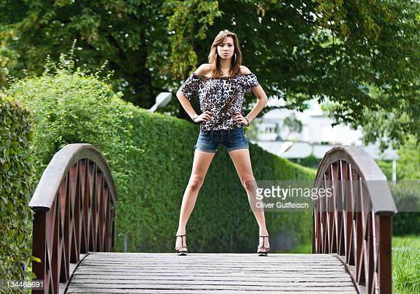 young woman wearing hot pants, leopard-print top and high heels posing confidently on curved wooden bridge - dark panthera stock pictures, royalty-free photos & images