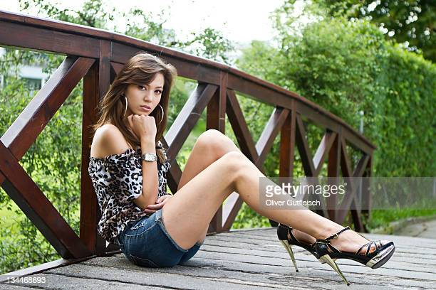 Young woman wearing hot pants, leopard-print top and high heels sitting down by the wooden balustrade of a wooden bridge