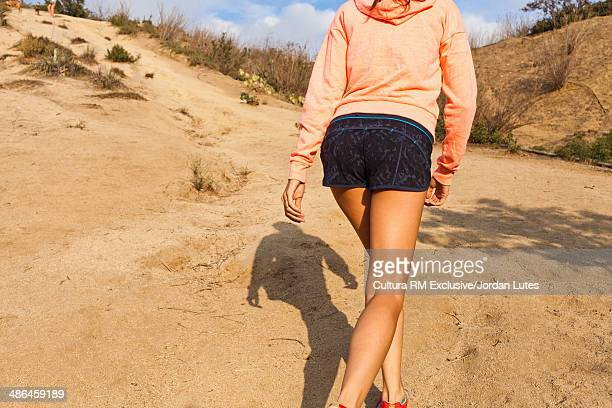 Young woman wearing hot pants walking uphill