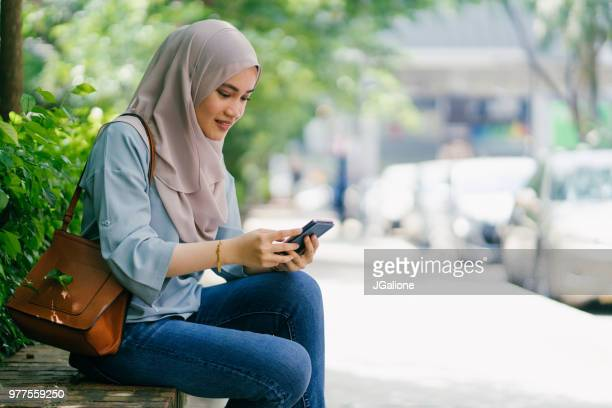 Young woman wearing in a hijab using a smartphone