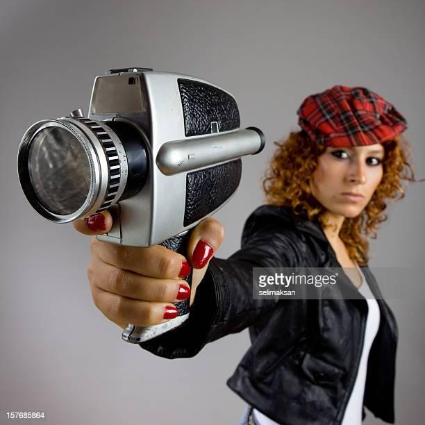 Young Woman Wearing jacket And Hat Aiming Camera As Gun