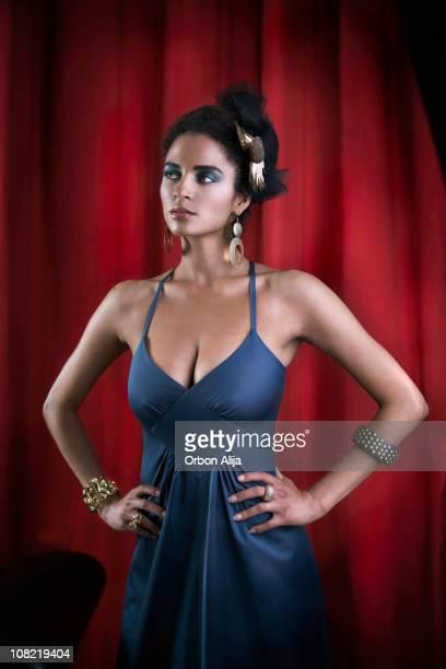 Jeune femme portant des bijoux posant avec les mains sur les hanches