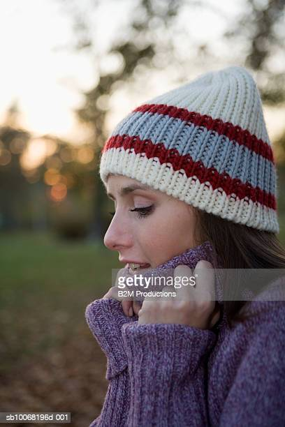 Young woman wearing jumper and hat in park, side view, close up