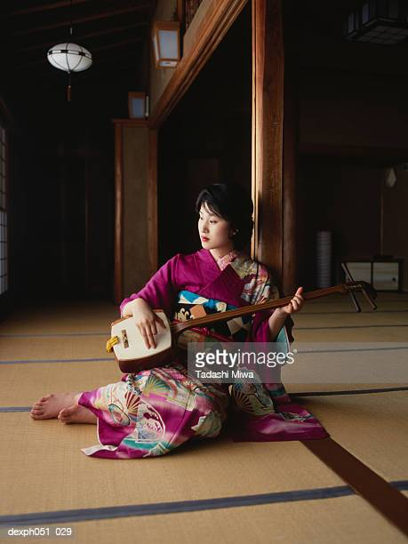 a young woman wearing kimono plays 'samisen' - shamisen stock photos and pictures