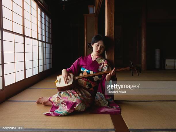 a young woman wearing kimono plays 'samisen' - vangen imagens e fotografias de stock