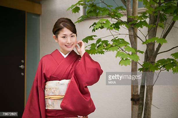 A young woman wearing kimono standing in front of door