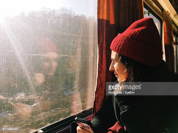 Young Woman Wearing Knit Hat Sitting In Train
