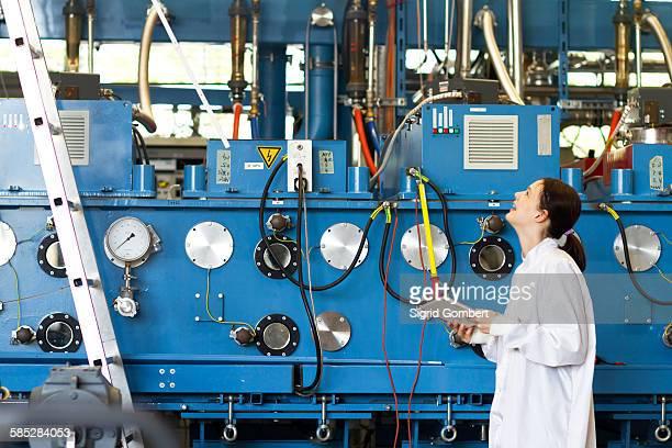 young woman wearing lab coat holding digital tablet, looking up at scientific equipment smiling - sigrid gombert fotografías e imágenes de stock