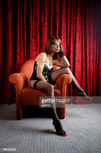 young woman wearing lingerie and sitting on chair - women in stockings and high heels stock photos and pictures