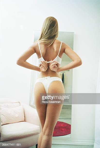Young woman wearing lingerie in dressing room, rear view