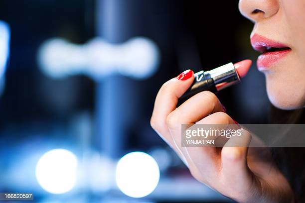 Young woman wearing lipstick and looking in mirror