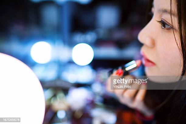 young woman wearing lipstick before shooting - far east stock photos and pictures