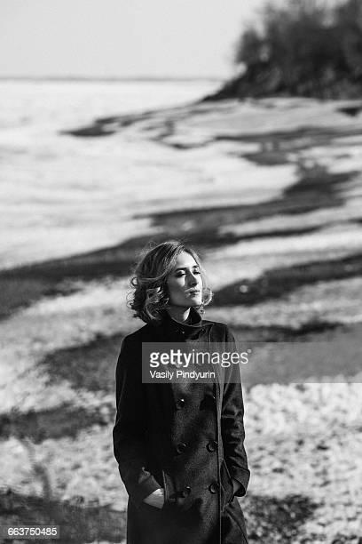Young woman wearing long coat walking on field
