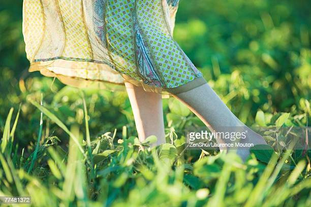young woman wearing long dress walking across grass, close-up, knee down - long dress stock pictures, royalty-free photos & images