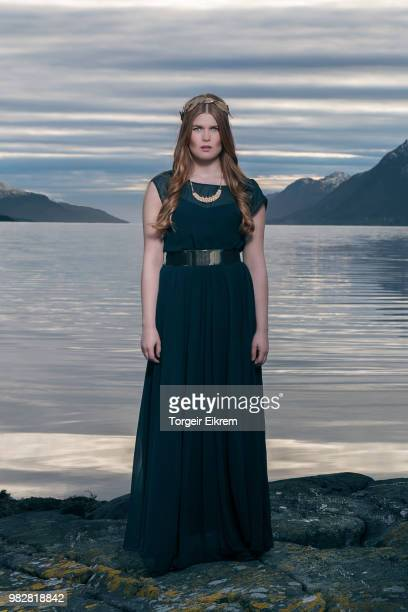 Young woman wearing long navy dress and gold crown against sea and mountains, Norway