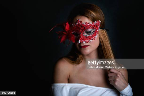 young woman wearing mask against black background - black mask disguise stock pictures, royalty-free photos & images
