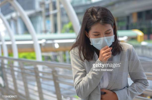young woman wearing mask and feeling sick - cough stock pictures, royalty-free photos & images