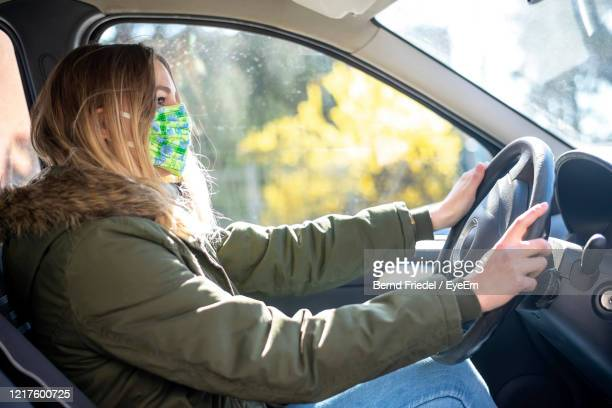 young woman wearing mask driving car in city - driving mask stock pictures, royalty-free photos & images