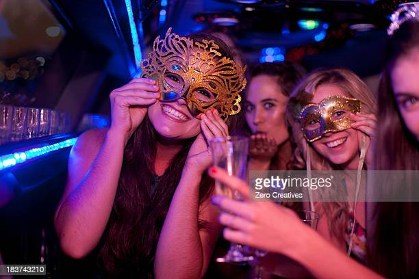 Young woman wearing mask in limousine