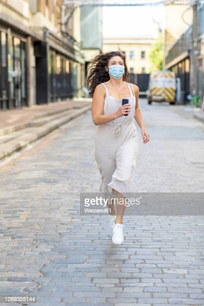 young woman wearing mask running on street in city - sleeveless stock pictures, royalty-free photos & images