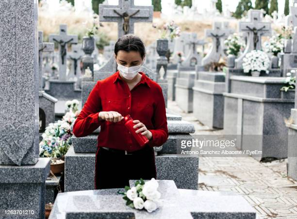 young woman wearing mask standing at cemetery - cemetery stock pictures, royalty-free photos & images