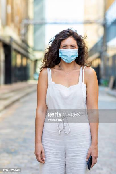 young woman wearing mask standing on street in city - sleeveless stock pictures, royalty-free photos & images
