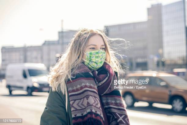 young woman wearing mask standing on street - scarf stock pictures, royalty-free photos & images