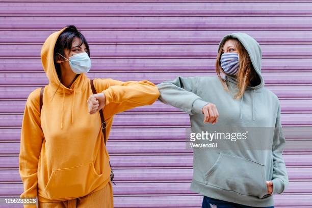 young woman wearing masks greeting with elbow - greeting fotografías e imágenes de stock
