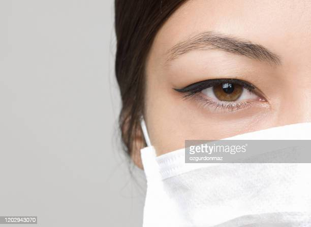 young woman wearing medical face mask, studio portrait - viral infection stock pictures, royalty-free photos & images