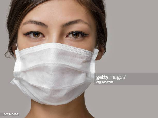 young woman wearing medical face mask, studio portrait - face masks imagens e fotografias de stock