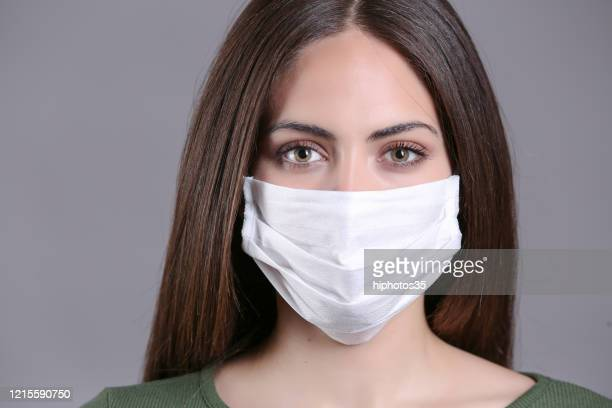 young woman wearing medical face mask, studio portrait - obscured face stock pictures, royalty-free photos & images