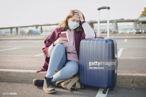 young woman wearing medical mask, with a suitcase - tourist stock pictures, royalty-free photos & images