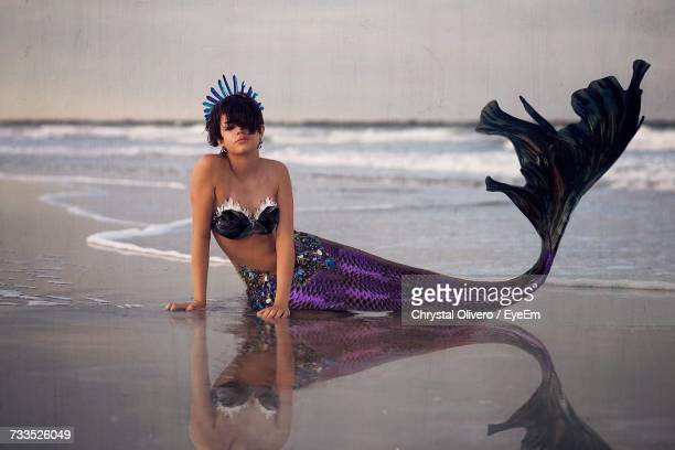Young Woman Wearing Mermaid Costume Resting On Sea Shore At Beach