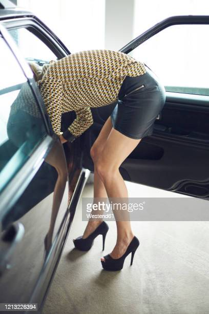 young woman wearing mini skirt leaning into a car - bending over in skirt stock pictures, royalty-free photos & images