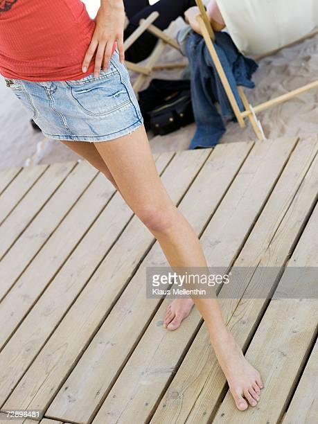 young woman wearing miniskirt standing on pier, low section, elevated view - girls barefoot in jeans stock photos and pictures