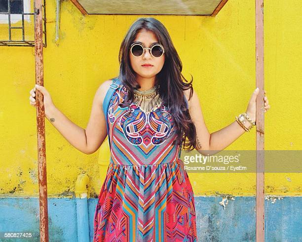 Young Woman Wearing Multi Colored Dress And Sunglasses Standing Against Wall