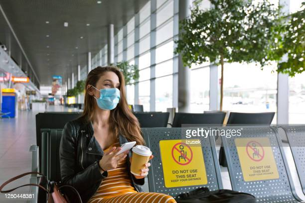 young woman wearing n95 face mask waiting in airport area - aeroplane stock pictures, royalty-free photos & images