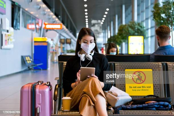 young woman wearing n95 face mask waiting in airport area - airport stock pictures, royalty-free photos & images