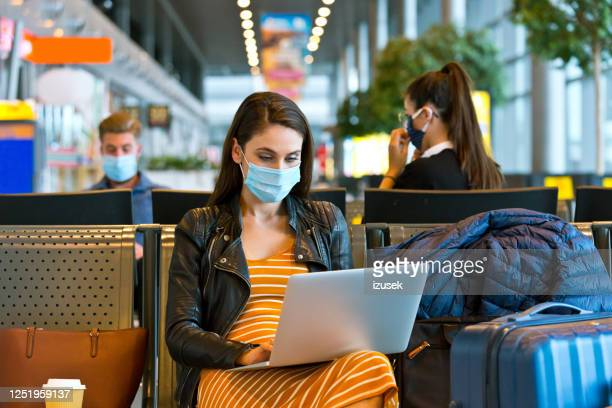 young woman wearing n95 face mask waiting in airport area - waiting stock pictures, royalty-free photos & images