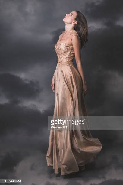 young woman wearing nude-colored evening dress - evening gown stock pictures, royalty-free photos & images