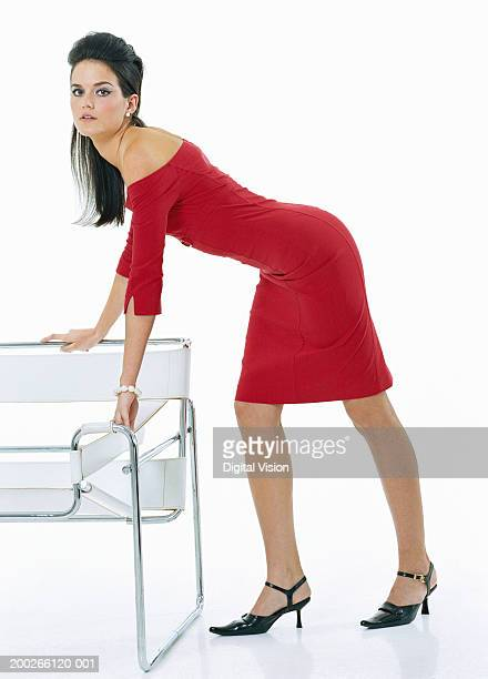 young woman wearing off the shoulder dress, leaning on chair, portrait - beautiful women bent over stock photos and pictures